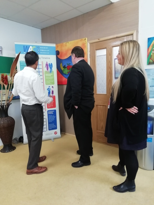 Image of Paige Cowling, Sajeed Mahmood and Mark Burns-Williamson OBE, looking at our NHS Screening Timeline.